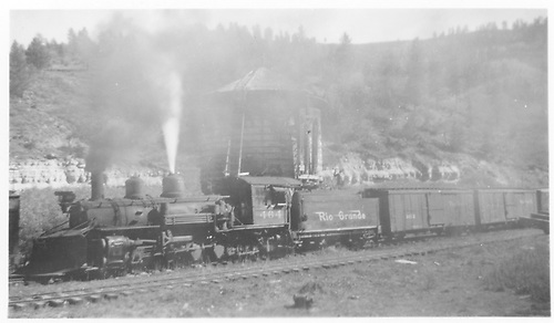Fireman side view of K-27 #464 popping steam with a northbound freight at the Brown water tank.<br /> RGS  Brown, CO  Taken by Radcliffe, William H. - 10/8/1950