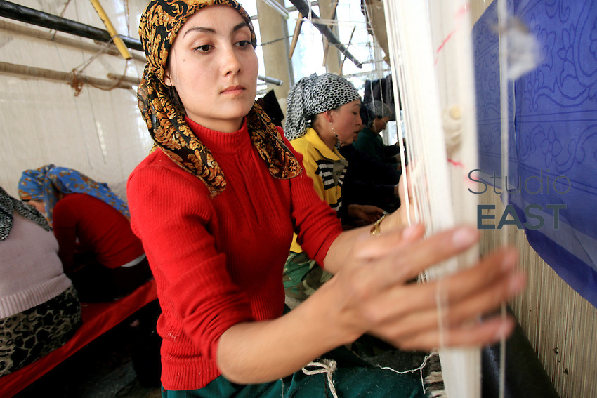 XINJIANG PROVINCE, CHINA - October 13: Female workers sew a carpet in Hetian Foreign Trade Carpets Workshop factory on October 13, 2006 in Hetian, Xinjiang province, China. (Photo by Servais Mont/Getty Images)