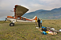 Pilot dirk nickisch with coyote air and his de-havilland beaver bush plane on tundra tires in the Brooks Range, Arctic, Alaska, dropping off hikers and their gear.