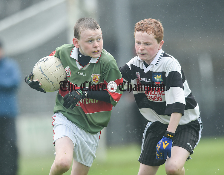 John Conneally of Clooney-Quin in action against Aaron Hayes of Clarecastle during the U-12 football finals in Cusack park. Photograph by John Kelly.