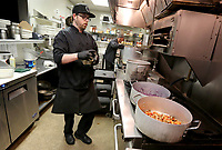 Corey McCain, executive chef at Bordinos, prepares a free family meal for laid off employees and family members to pick up Thursday, March 19, 2020, at the restaurant on Dickson Street in Fayetteville. Restaurants, bars businesses in the city of Fayetteville are making adjustments because of the spread of covid-19. Check out nwaonline.com/200322Daily/ and nwadg.com/photos for a photo gallery.<br /> (NWA Democrat-Gazette/David Gottschalk)