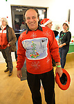 A smiling man wears a festive colorful Christmas sweater at the Jingle Boom Holiday Bash, which awarded prizes to people wearing the most creative or Ugly Sweaters, at the Main Street Gallery of Huntington Arts Council. Sparkboom, an HAC project, provides events such as this geared to Gen-Y, 18-34 years of age, to address the 'brain drain' of creative young professionals of Long Island. The paintings on the art gallery walls were the Annual Juried Still Life Show.