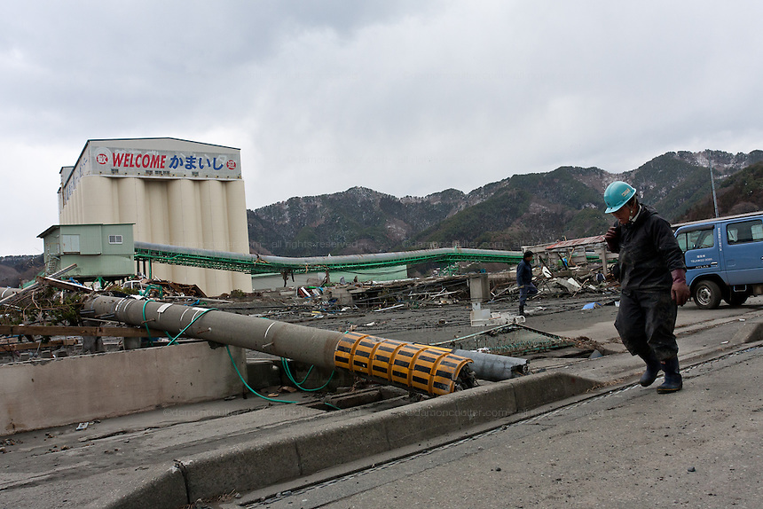 A man walks past the remains of an industrial complex after the tsunami that struck the north east coast of Japan on March 11th Kamaishi, Iwate, Japan. March 17th 2011