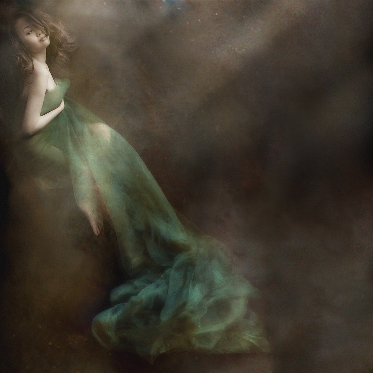 Naked young woman covered in long green fabric