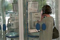 Woman phoning from a public telephone box in a city street.