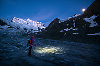 Crossing the Glacier de Corbassière at sunrise, and using a headlamp in the pre-dawn darkness, with Grand Combin the distance, Val de Bagnes, Switzerland