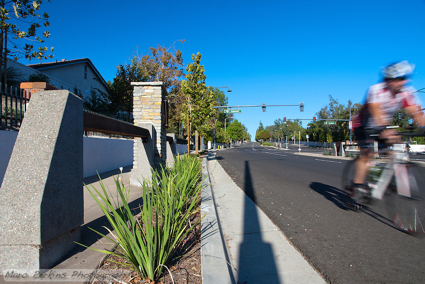 """A bicyclist races downhill past the new parkway treatment at the Grand and Longview intersection. This was part of the 2015 rebuild of the Grand Avenue and Longview Drive intersection for Diamond Bar's 2015 """"Grand Avenue Beautification"""" project, landscape architecture for the project was by David Volz Design."""