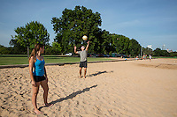 A young couple enjoy in summer vacation playing volleyball at Zilker Park sand volleyball courts in Austin, Texas on a beautiful summer day.