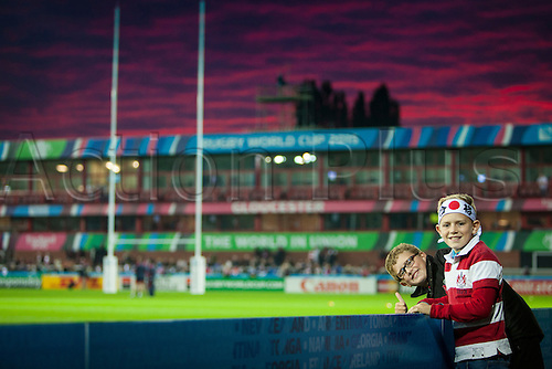 11.10.2015. Kingsholm Stadium, Gloucester, England. Rugby World Cup. USA versus Japan. Two young supporters pose in front of a sunset at Kingsholm Stadium before kickoff.