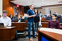 """Sam Carson, 28, (center in front), and Arianna Grand (standing center right), 27, take care of last minute details before New York Assemblyman (79th District) and Vice Chair of the Democratic National Committee Michael Blake speaks to a live audience during a session of Resistance School in the Starr Auditorium in the Belfer Building of Harvard University's John F. Kennedy School of Government, on Thurs., April 27, 2017. Carson led the Resistance School logistics group volunteers before the lecture. Carson and Grand are Master in Public Policy grad students at the Kennedy School. Blake's lecture was titled """"How to sustain the resistance long term.""""  The lecture, which was the fourth such session and the final in what the group calls the """"first semester"""" of Resistance School, was also streamed live on the internet. Resistance School was started by progressive graduate students at Harvard after the Nov. 8, 2016, election of President Donald Trump. Resistance School describes itself as a """"practical training program that will sharpen the tools [needed] to fight back at the federal, state, and local levels."""" The live lectures are streamed and archived online alongside other information on the Resistance School website. During the lectures, teams of volunteers engage with followers on social media, including Facebook and twitter, sharing soundbytes, quotations, and supplementary materials as the lectures happen."""