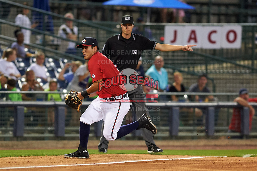 Mississippi Braves third baseman Rio Ruiz (5) fields a ground ball as umpire Clint Vondrak signals fair during a game against the Pensacola Blue Wahoos on May 28, 2015 at Trustmark Park in Pearl, Mississippi.  Mississippi defeated Pensacola 4-2.  (Mike Janes/Four Seam Images)