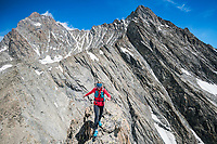 A trail runner moving quickly on a rock ridge on the Strahlegghorn, with the Schreckhorn and Lauteraarhorn in the background. Grindelwald, Switzerland.