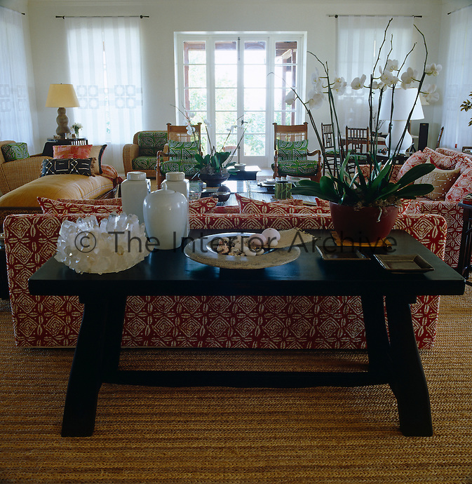 An Indonesian table positioned behind one of the sofas in the living room displays a collection of Asian ceramics