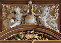 Putti in carved stucco holding the initial F and a golden salamander in the flames, symbol of King Francois I, decoration by Rosso Fiorentino, 1535-37, in the Galerie Francois I, begun 1528, the first great gallery in France and the origination of the Renaissance style in France, Chateau de Fontainebleau, France. The Palace of Fontainebleau is one of the largest French royal palaces and was begun in the early 16th century for Francois I. It was listed as a UNESCO World Heritage Site in 1981. Picture by Manuel Cohen