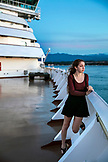 CANADA, Vancouver BC, A young female passenger watches the sunset off the Holland America cruise ship, the Oosterdam, while it cruises the Inside Passage from Vancouver BC to Ketchikan, Georgia Straight, British Columbia