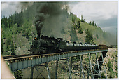 3/4 view of engine #497 pulling 6 tank cars, box cars, gondolas and others across Cascade Trestle.<br /> C&amp;TS  Cascade Trestle, CO