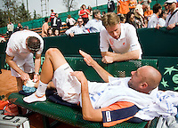 12-4-08, Macedonie, Skopje, Daviscup, Macedonie- Nederland, Doubles Peter Wessels wordt getaped door fysio Edwin Visser nadat hij zijn enkelbanden heeft gescheurt, captain Jan Siemerink kijkt bezorgd toe