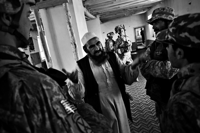 Lt. Sam Lyon (L), of 2nd Platoon, Bravo Company, 1-32 Infantry, 3rd Brigade, 10th Mountain Division, talks with an Imam at a mosque in Charkh, Afghanistan, Saturday, May 16, 2009.