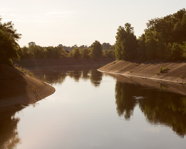August 6, 2016. Flint, Michigan.<br />  The Flint River, downstream from downtown. <br />   In April 2014, the city of Flint switched its water source from the Detroit Water and Sewerage Department to using the Flint River in an effort to save money. When the switch occurred, the city failed to have corrosion control treatment in place for the new water. This brought about a leaching of lead from pipes into the water, increasing the lead content in the drinking water to levels far above legal limits. After independent sources brought this to light, the city admitted the water was unsafe and legal battles have ensued between resident and the local and state governments.
