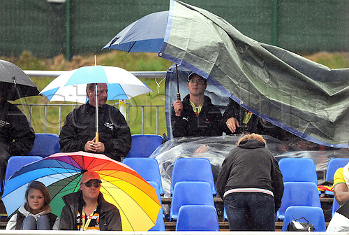 Spectators stand in the rain at the race track during qualifying at Spa-Francorchamps Circuit near Spa, Belgium