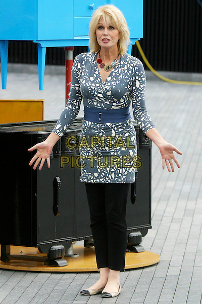 JOANNA LUMLEY .The launch of the old furniture recycling scheme, The Scoop, More London, the Queen's Walk, London, England. .July 12th, 2010 .full length black grey gray white print top blue waist belt trousers leggings hands.CAP/JEZ.©JEZ/Capital Pictures.