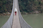 A woman carries a bag of grain across a suspension bridge at Majhitar, a village in the Dhading District of Nepal.