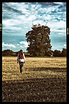 Young teen girl walking alone in a field after harvest under blue sky with soft focus