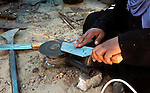 Aysha Ali, the wife of Ibraheem Mustafa, a 40-year-old Palestinian blacksmith, sharpens a handmade knife, at their small workshop in Gaza city on April 30, 2015. The ILO estimates that the 2014 conflict in Gaza raised unemployment from 32.6 per cent to 36.9 per cent, which caused an estimated daily loss in economic activity of US$ 508,000 per working day since August 2014. As the numbers of the unemployed laborers in Gaza reached 200,000 and poverty to 60 per cent, according to local reports. Photo by Ashraf Amra