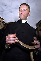 """The parish priest  of Cocullo with snakes in hand before the procession.The feast of snakes. Process dedicated to the Saint Dominic, in the streets of Cocullo, in the Abruzzo region, Italy on May 1, 2019.<br /> <br /> <br /> <br /> The St. Domenico's procession in Cocullo, central Italy. Every year on the first  of May, snakes are placed onto the statue of St. Domenico and then the statue is carried in a procession through the town. St. Domenico is believed to be the patron saint for people who have been bitten by snakes:<br /> <br /> Italy, Cocullo, in the Province of L'A...quila, is at 870 meters a.s.l., along the railway line connecting Sulmona to Rome. The village rises alongside Mount Luparo (1327 meters) """"The valley opening in front of the village is surrounded by bare rocks, while on the other side, to the south, snow-capped mountain crests follow one after the other...""""<br /> San Domenico Abate lived in the 10th and 11th centuries AD. Born in Foligno, in the Umbria region, he started his pilgrimages, preaching and ascetic practices in Central Italy, making miracles recorded by the word-of-mouth tradition. He died on 22 January 1031 and was buried in Sora.<br /> <br /> Cocullo snake charmers are over with their snake hunting. They proceeded through the During the procession on the first in May, before the snakes are placed all over the statue of St. Dominick, they will be fed with milk kept in containers with crusca. It is the snake that, most of all other elements, expresses an ancestral myth: the unknown aspect and unpredictability of the natural environment with man's innate need to achieve the dominance on his own habitat. <br /> <br /> Snakes and wolves were the emblems of Italic peoples like the Marsians and Irpinians. Some areas in Abruzzo, especially in the Sagittario valley, were under the menace of wolves and snakes, which for the local populations represented the uncertainty and anxiety of their existence that, together with the precariousness and """