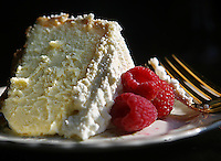 A slice of cheesecake with fresh raspberries
