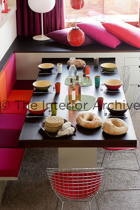 The vibrant colours of the soft furnishings and the lacquered bamboo crockery give the dining room a fun, youthful feel