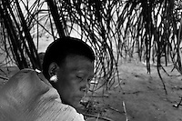 A Nukak woman, with a white feather in her ear, lies in a hammock in a refugee encampment close to San Jose del Guaviare, Colombia, 4 September 2009. The Nukak Maku people, nomadic hunter-gatherers from Amazonia, were violently driven out of the jungle by the Colombian guerilla and paramilitary squads. Now, roughly cut off their original tribal lifestyle, they stuck between worlds. They learn from the (mainly Christian) aid workers to use clothes, to listen to the radio, to beg for money. Although their digestion suffer, they love to eat sweets, cookies and other western food. They have hunted out all the animals around and now there is nothing left for them. Nukak can not return to the jungle, their world has already passed through an irreversible change.