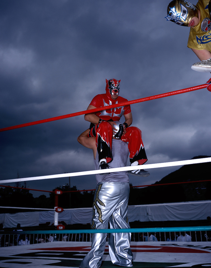 """Male """"Luchadores"""" (wrestlers) wrestle in Ecatepec, on the outskirts of Mexico City.  Their match is a warm-up for the women wrestling. Stormy skies add drama to the event. June 2004"""