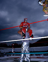 "Male ""Luchadores"" (wrestlers) wrestle in Ecatepec, on the outskirts of Mexico City.  Their match is a warm-up for the women wrestling. Stormy skies add drama to the event. June 2004"