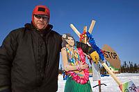 Volunteer checker Jim Gallea poses w/*Aloha* themed welcome sign @ Cripple chkpt 2006 Iditarod