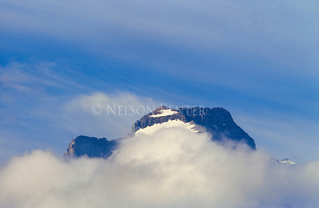 A mountain peak rises above the clouds in Glacier National Park in Montana