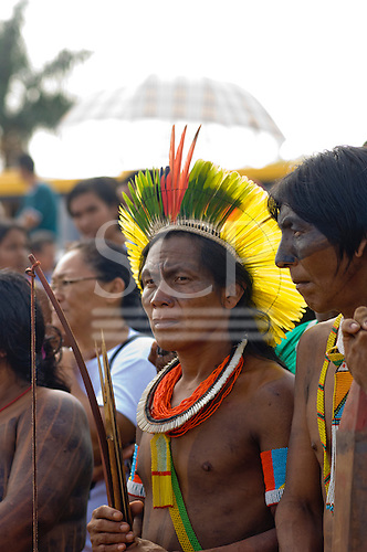 Altamira, Brazil. Kayapo Indian warrior carrying a bow and arrows and wearing a cocaa feather headdress.