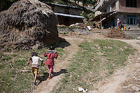 Children carry a bottle of drinking water from a fountain in the village of Sudal, outside of Kathmandu, Nepal. May 05, 2015