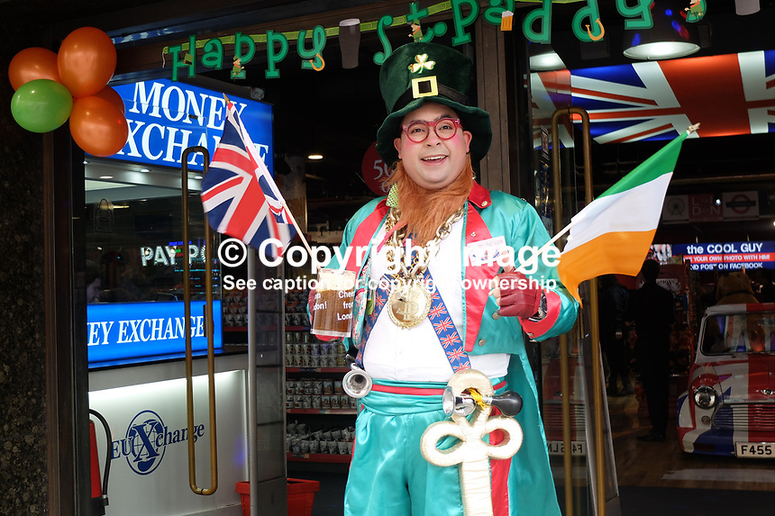 More people celebrate St Patrick&rsquo;s Day that were born in Ireland or are of Irish extraction. It&rsquo;s an excuse to celebrate worldwide usually in excess. This guy In Piccadilly, London, uses it to promote his bureau de change wearing an outfit of a type never worn in Ireland. 17th March 2017. 201703173338<br /> <br /> Copyright Image from Victor Patterson, 54 Dorchester Park, <br /> Belfast, UK, BT9 6RJ<br /> <br /> t1: +44 28 9066 1296 (from Rep of Ireland 048 9066 1296)<br /> t2: +44 28 9002 2446 (from Rep of Ireland 048 9002 2446)<br /> m: +44 7802 353836<br /> <br /> e1: victorpatterson@me.com<br /> e2: victorpatterson@gmail.com<br /> <br /> www.victorpatterson.com<br /> <br /> Please see my Terms and Conditions of Use at www.victorpatterson.com. It is IMPORTANT that you familiarise yourself with them.<br /> <br /> Images used on the Internet must be visibly watermarked i.e. &copy; Victor Patterson within the body of the image and copyright metadata must not be deleted. Images used on the Internet have a size restriction of 4kbs and will be chargeable at current NUJ rates unless agreed otherwise.<br /> <br /> This image is only available for the use of the download recipient i.e. television station, newspaper, magazine, book publisher, etc, and must not be passed on to any third party. It is also downloaded on condition that each and every usage is notified within 7 days to victorpatterson@me.com<br /> <br /> The right of Victor Patterson to be identified as the author is asserted in accordance with The Copyright Designs And Patents Act (1988).