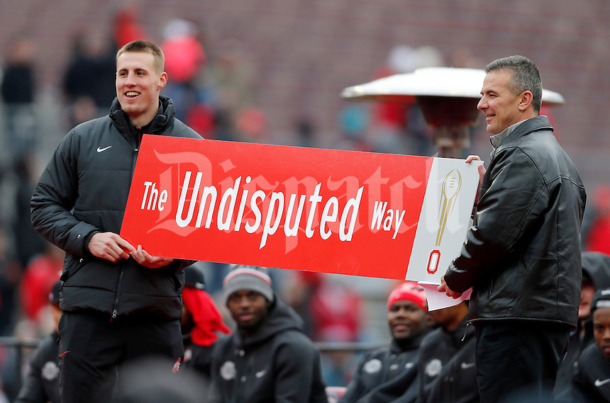Tight end Jeff Heuerman and coach Urban Meyer hold a sign that will be placed on High Street during the Ohio State football National Championship celebration at Ohio Stadium on Saturday, January 24, 2015. (Columbus Dispatch photo by Jonathan Quilter)