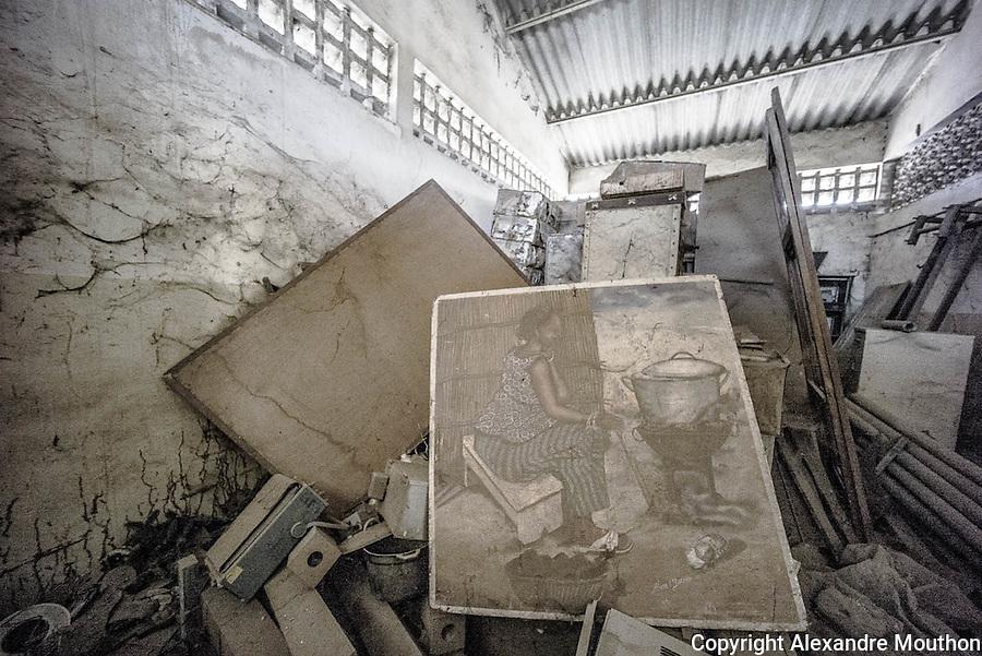 """Les archives, entassées sans protection, se décomposent dans un hangar. L'illustration centrale est emblématique d'un des premiers enjeux énergétiques en Afrique. En zone sahélienne, la forte consommation de bois domestique et la déforestation qui en résulte, sont une atteinte aux équilibres environnementaux et sociaux. Dès les années 1960, des """"cuisinières"""" solaires ont été mises au point pour tenter d'enrayer le phénomène."""