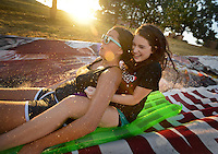 NWA Democrat-Gazette/BEN GOFF &bull; @NWABENGOFF<br /> Ashlea Witt, 16, (left) and Lauren Moore, 15, take a ride down a roughly 150 yard waterslide on Saturday Aug. 1, 2015 at the home of Hutch Kufahl in Bentonville. Kufahl, youth pastor at First Baptist Church of Bentonville, organized the waterside as an activity for his Studio 412 high school youth group.