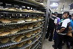 Palestinians wait in line at a bakery to buy bread in Gaza City on July 21, 2014. World efforts to broker a ceasefire in war-torn Gaza gathered pace as Israel pressed a blistering 14-day assault on the enclave, pushing the Palestinian death toll to 558. Photo by Mohammed Asad
