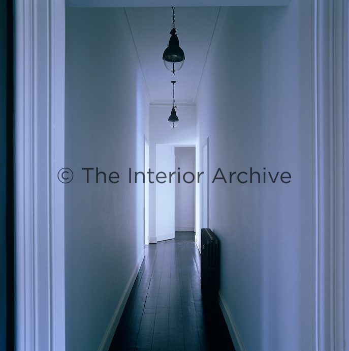 Light pours in through the open doors on to the dark polished floorboards in this upstairs corridor