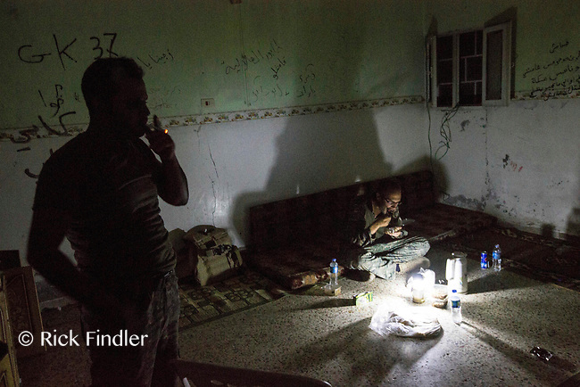 August 2017. YPG Media Centre, Raqqa, Syria.<br /> Foreign volunteer fighter 'Macer Gifford' (right)eats dinner on the floor of his nocter on the front lines of western Raqqa.<br /> The MFS (Syriac Military Council) are a group of Assyrian Christians who fight alongside the Syrian Democratic Forces in the fight to topple ISIS.<br /> Photographer: Rick Findler