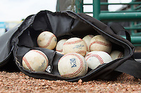 A bag of baseballs sits outside the visitors dugout prior to the South Atlantic League game between the Charleston RiverDogs and the Hickory Crawdads at L.P. Frans Stadium on May 25, 2014 in Hickory, North Carolina.  The RiverDogs defeated the Crawdads 17-10.  (Brian Westerholt/Four Seam Images)