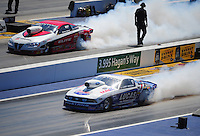 Apr. 14, 2012; Concord, NC, USA: NHRA pro stock driver Larry Morgan (near lane) does his burnout alongside Rickie Jones during qualifying for the Four Wide Nationals at zMax Dragway. Mandatory Credit: Mark J. Rebilas-