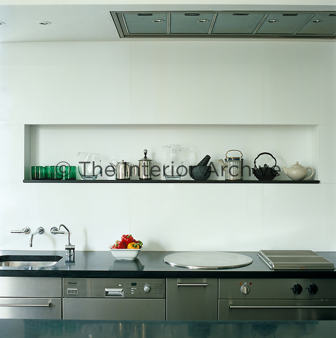 This contemporary well-organised kitchen has units of stainless steel with tops of black slate