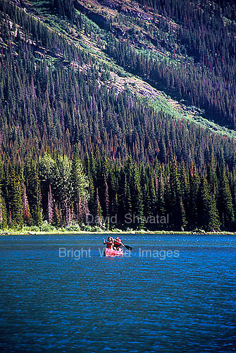 Tourists on vacation paddle a canoe through Swiftcurrent Lake at Many Glaciers in Glacier National Park Montana USA