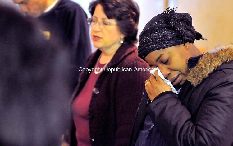 TORRINGTON, CT-13 JANUARY 2009-011310JS01-Joceline Dessalines, right, a member of the First French Speaking Baptist Church of Waterbury, wipes a tear as Marie Johnson, a member of the Waterbury Baptist Ministries, left, says a prayer for the people of Haiti during a prayer service Wednesday for those affected by Tuesdays Haitian earthquake.<br /> Jim Shannon Republican-American